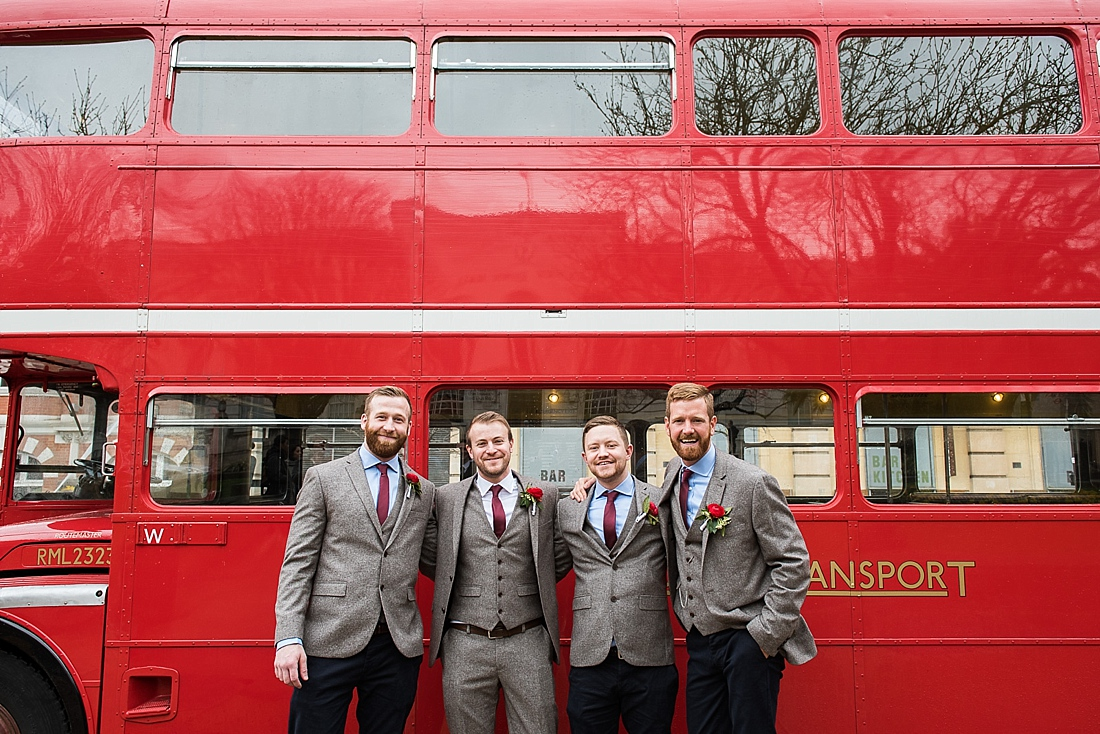 Groom with groomsmen outside red bus