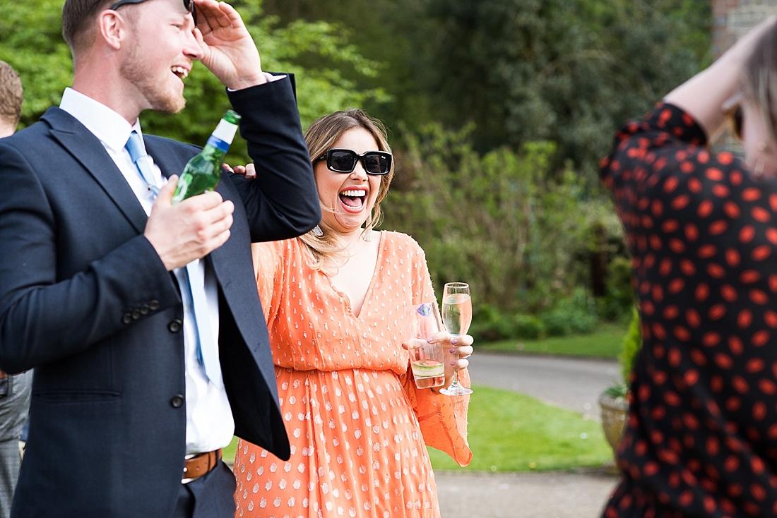 Laughing wedding guests enjoy sunshine