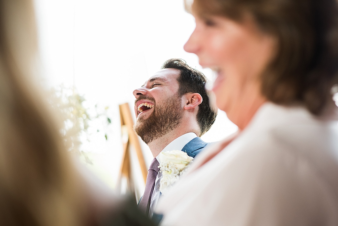 Captured moment groom and mum laughing during wedding speech