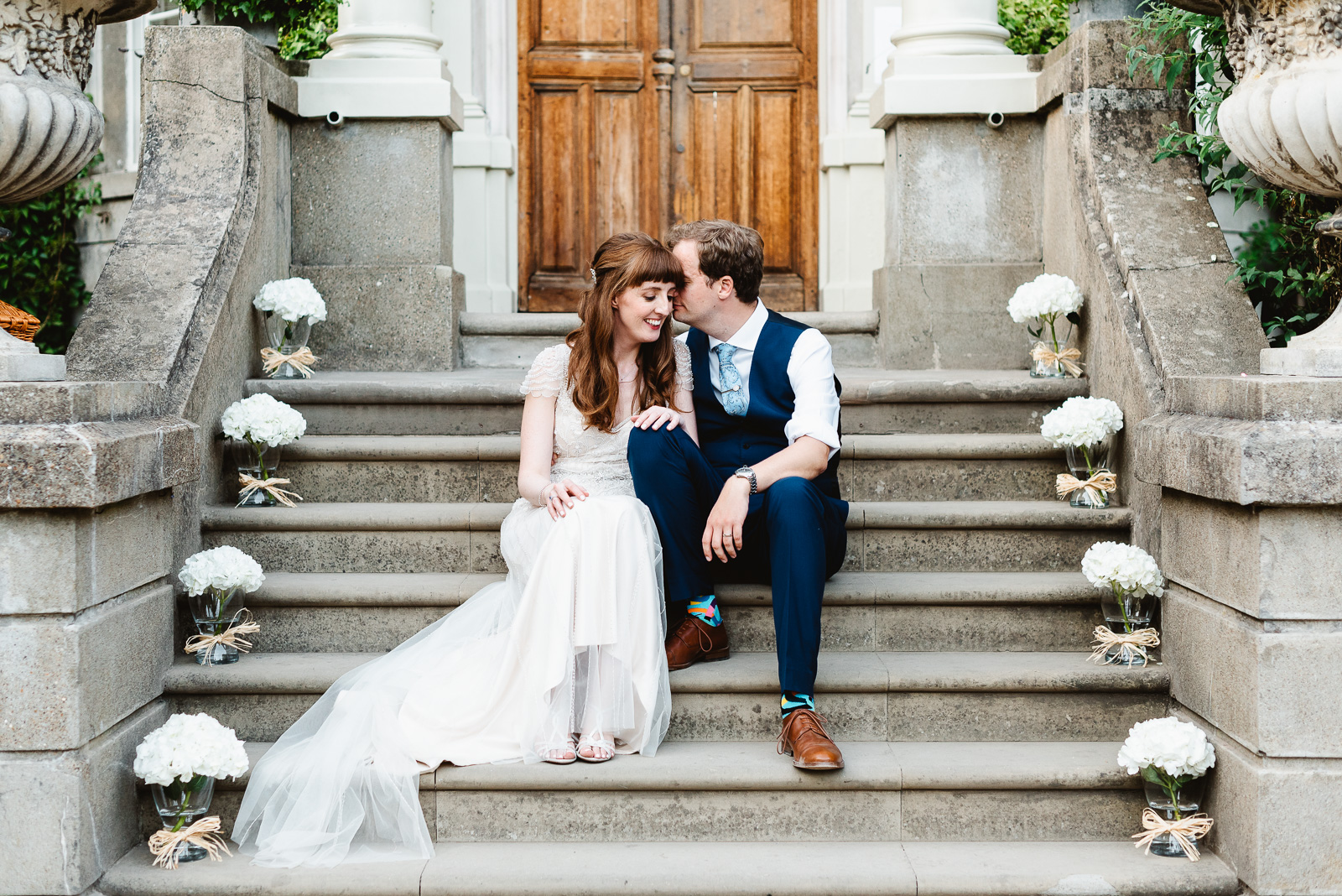 Bride-Groom-cuddling-hampton-court-house