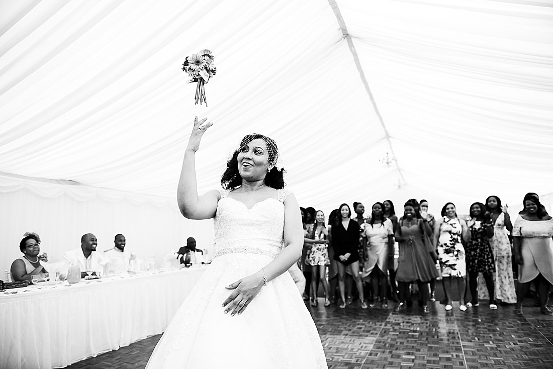 black bride throwing bouquet London wedding © Fiona Kelly Photography