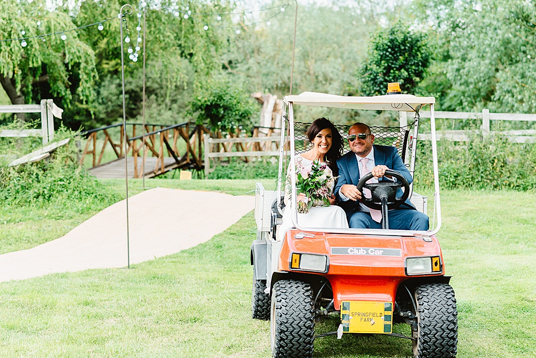 bride and groom arrive in golf buggy festival wedding